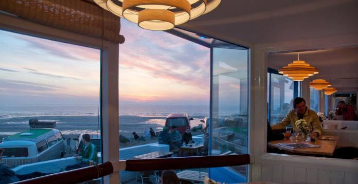 Large bay windows at blue bar, looking over the beach at Porthtowan, Cornwall, UK.